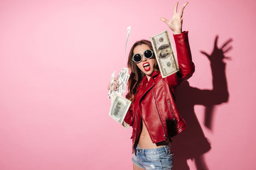 Portrait of a young happy woman winner throwing money banknotes