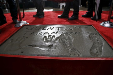 The hand, footprints and signature of director Quentin Tarantino in cement are pictured in the forecourt of the TCL Chinese theatre in Hollywood
