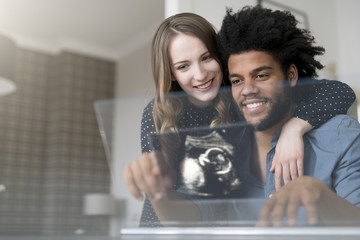 Smiling couple looking at ultra sound picture of baby on futuristic screen