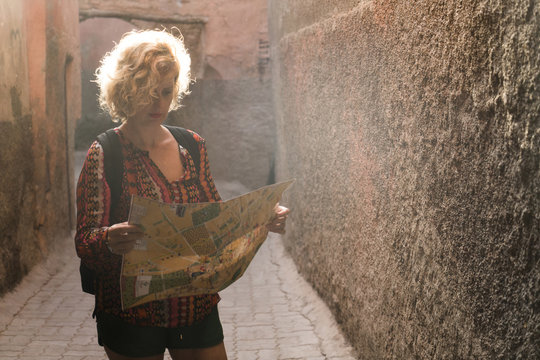 Morocco, Marrakesh, tourist standing in a passageway looking at map