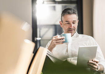 Portrait of businessman with cup of coffee sitting in his office using tablet