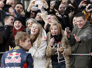 Fans react as Red Bull Formula One driver Sebastian Vettel of Germany approaches after a show run event in Milton Keynes
