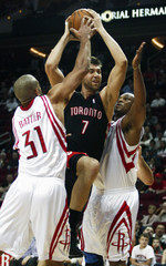 Raptors forward Bargnani is ganged up on by Rockets guards Battier and Hayes as he goes to the basket for a shot during the first half of their NBA basketball game in Houston