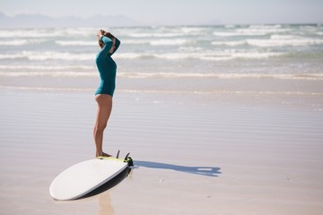 Female surfer standing on the beach with surfboard