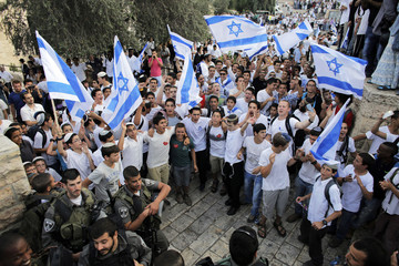 Youths wave Israeli flags near border policemen during a parade marking Jerusalem Day, in Jerusalem's Old City