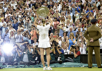 Petra Kvitova of the Czech Republic holds the winners trophy, the Venus Rosewater Dish, after defeating Eugenie Bouchard of Canada in their women's singles final tennis match at the Wimbledon Tennis Championships, in London