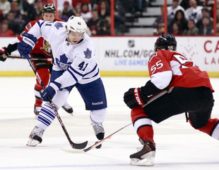 Toronto Maple Leafs' Kulemin attempts to move the puck past Ottawa Senators' Gonchar during the first period of their NHL hockey game in Ottawa