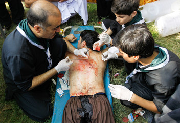 A man's back is stitched up by medics after self flagellation during the Shi'ite Muharram procession in Islamabad