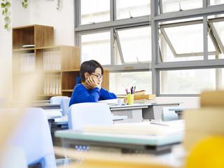 asian elementary schoolboy sitting alone in classroom