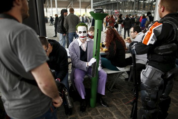 "A Paris Comic Con attendee dressed as the character ""Joker"" waits during the first day of the event in Paris"