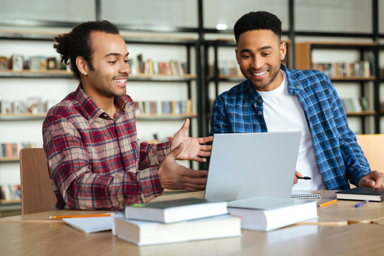 Two multicultural male students studying with laptop