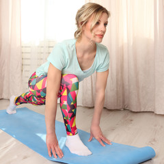 Attractive woman do fitness exercise at home on a blue mat in living room, morning time