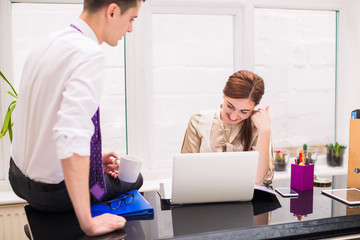 Young businesswoman smiles and sits at the table on which young businessman sits with cup of coffee at the office