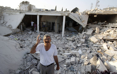 A man gestures in front of houses destroyed during a recent Syrian Air Force air strike in Azaz
