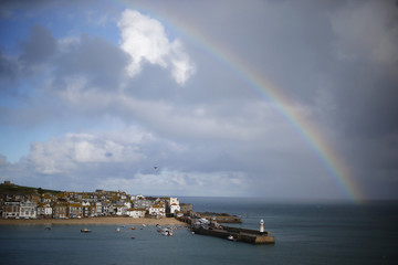 A rainbow forms as a squall moves past the harbour in St Ives in Cornwall