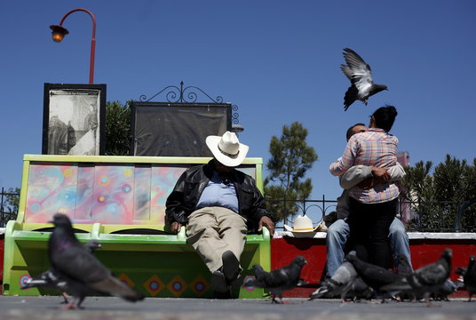 A couple embrace next to a man sleeping on a park bench in downtown Ciudad Juarez