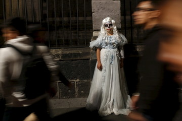 A girl dressed up as a dead woman is seen during the Catrinas parade in Mexico City