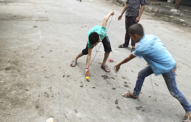 Boys play with traditional spinning tops on a street in Aleppo's al-Sakhour district