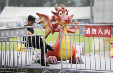 A security guard looks at his mobile phone next to a sculpture of a dragon character from a cartoon in Beijing