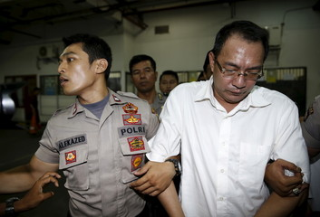 An Indonesian policeman guards drug dealer Wong Chi Ping as he arrives at a court room for his trial in West Jakarta district court