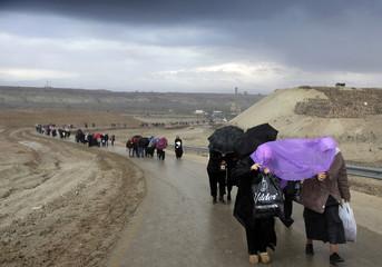 Orthodox pilgrims walk away from a baptismal site near Jericho