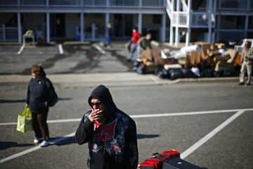 Residents line up to board buses after salvaging through their homes that were damaged by Hurricane Sandy in Seaside Heights