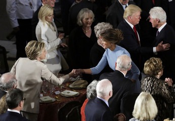 Hillary Clinton greets Melania Trump as her husband Bill Clinton speaks with Donald Trump during the Inaugural luncheon in Washington