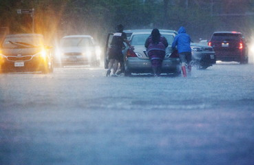 People push a stranded car through a heavily flooded road in downtown Houston