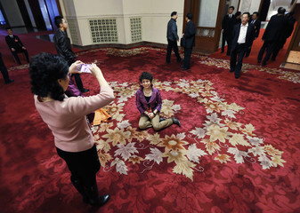 A female delegate has a souvenir picture taken at the Great Hall of the People