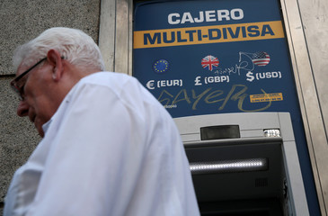 A man walks past a currency exchange ATM in Madrid