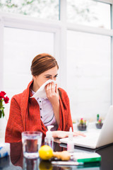 Portrait of young sick office worker who sits at the table with medicaments at the office, keeps napkins in hand and wipes nose
