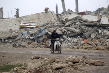 A man drives a motorcycle near rubble of damaged buildings in al-Rai town