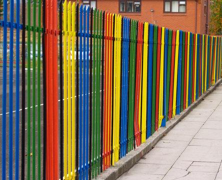 Multi-coloured fence surrounding infant school premises in the UK