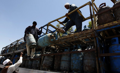 Libyan men unload gas cylinders from a truck provided by the Libyan Rebel National Transitional Council in Ajdabiyah