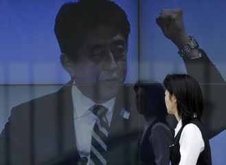 A woman walks past an electronic board displaying a photo of Japan's Prime Minister Shinzo Abe, a part of news of Abenomics, in Tokyo