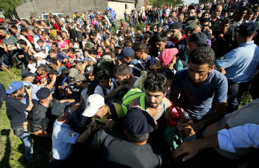 Migrants push policemen as they attempt to board buses in Tovarnik