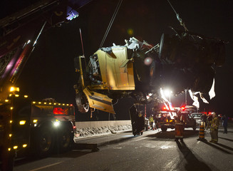 A crane hoists the cab of a truck which left Highway 401 and plunged into a river near Woodstock