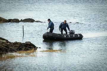 Members of a NYPD dive team drive their boat to the shore after a search for human remains at the East River in the Queens borough of New York