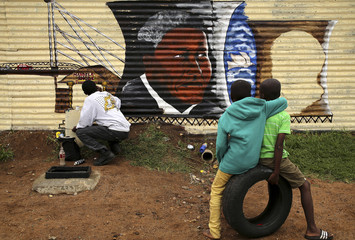 Boys watch as artist Siya Mbola paints a mural of former South African president Nelson Mandela in Soweto