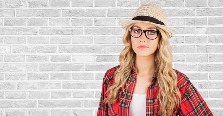 Female hipster wearing hat against wall