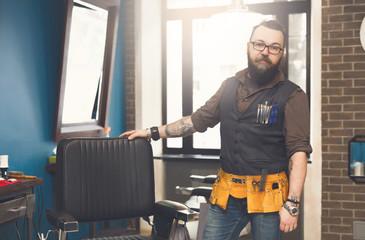 Bearded barber posing to camera at barbershop