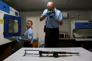 A French gendarme working for the UN photographs an AK-47 used by gunmen in the Radisson Blu hotel attack on a table in a lab in Bamako
