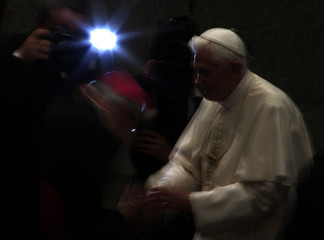Pope Benedict XVI is greeted by a cardinal during his weekly Wednesday general audience in Paul VI hall at the Vatican