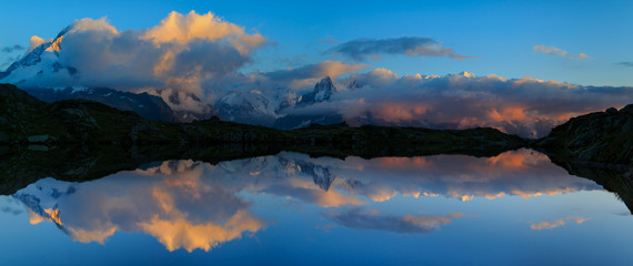 Fotomurales - Mountains and clouds reflected in Lac De Cheserys, near Chamonix, France.