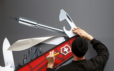 A worker sticks a picture of a Swiss army knife on a window of the new flagship store of Swiss knife producer Victorinox in Zurich