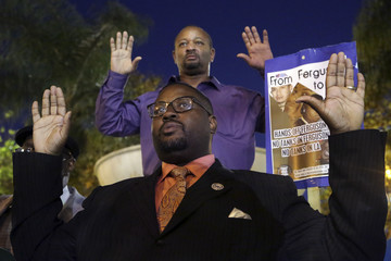 Tulloss and community activist Ali hold up their arms during a demonstration in Los Angeles, California, following grand jury decision in the shooting of Brown in Ferguson, Missouri
