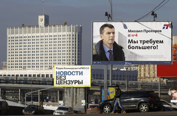 A presidential campaign poster for Russian billionaire Mikhail Prokhorov is on display, with the Russian White House, headquarters of the federal government, seen in the background, in Moscow