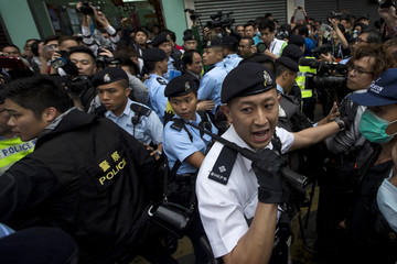 A police officer holds a baton during a demonstration against mainland traders, at Yuen Long in Hong Kong