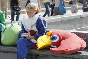 A woman dressed as a cartoon woodpecker character rests and counts her money at the central square of Kiev