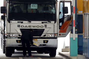 A South Korean truck driver returning from the Kaesong Industrial Complex (KIC) inside the North Korean border, changes his license plate authorized by North Korea to a South Korean one upon his arrival at the South's CIQ in Paju